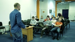 Man talking with a small group of students in a audience Stock Footage