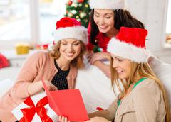 women in santa helper hats with card and gifts - stock photo