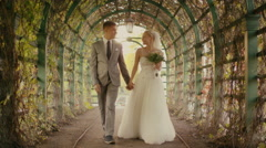 Happy young newlyweds are walking in a park - stock footage
