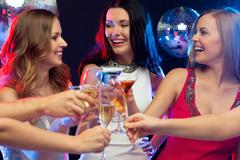 three smiling women with cocktails in club - stock photo