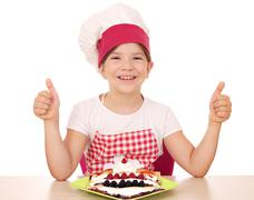 Happy little girl cook with crepes and thumbs up Stock Photos