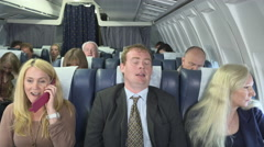 Plane passengers upset and annoyed at woman using cell phone - stock footage
