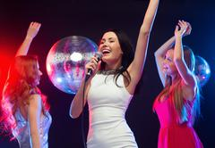 three smiling women dancing and singing karaoke - stock photo