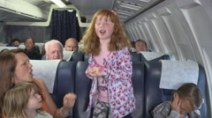 Child will not behave on flight mother trying to get her to sit down Stock Footage