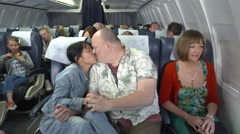 Romantic couple kissing on plane annoy other passengers - stock footage