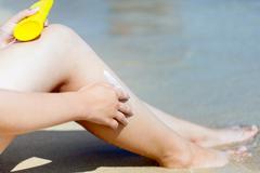 Sun protection cream on the leg Stock Photos