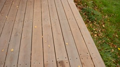 sweeping leaf off wooden patio and onto lawn in autumn - stock footage