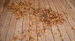sweeping leaf in a pile on patio in autumn using broom - stock footage