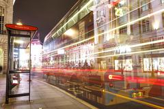 Long exposure at a bus stop on the Piccadilly circus. No faces, just long lights - stock photo