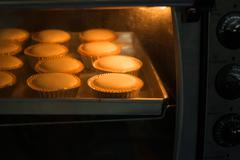 Baked cup cakes on a tray in the oven Stock Photos
