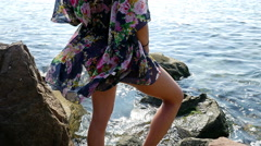 Young woman in a colorful summer dress admiring the sea on the rocky shore Stock Footage
