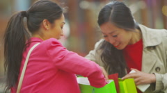 Attractive Asian female friends with colourful bags looking at their purchases Stock Footage