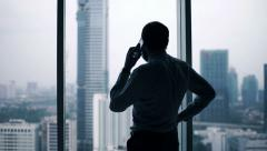 Young businessman talking on cellphone by window in office - stock footage