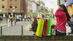 Attractive Asian woman with colourful shopping bags talking on mobile phone outd Stock Footage