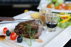 Delicious beef steaks on white plate - stock photo