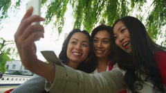 Attractive Asian female friends take a selfie with mobile phone outdoors Stock Footage