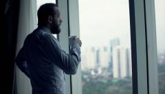 Young businessman drinking coffee and admire view from window - stock footage