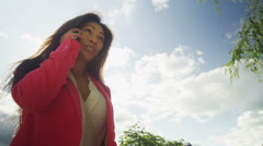 Attractive Asian woman talking on mobile phone as she walks through the city Stock Footage