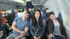 Male plane passenger falls asleep on shoulder of female passenger Stock Footage