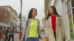 Attractive Asian female friends walking with colourful bags in busy shopping are Stock Footage