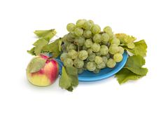 Still life a plate with grapes and one apple at the left, isolate Stock Photos
