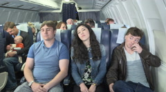 Male passenger on plane smiling when pretty female passenger falls asleep on him Stock Footage