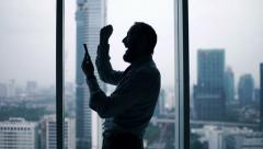 Happy businessman reading good news on smartphone standing by window Stock Footage