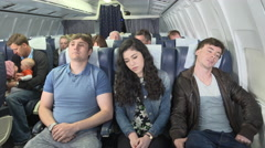 Female passenger on flight falls asleep on man next to her Stock Footage