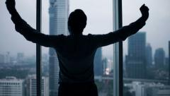 Young businessman stretching his arms, neck and admire view from window Stock Footage