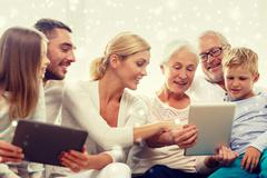 smiling family with tablet pc computers at home - stock photo