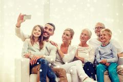 Happy family taking selfie with smartphone at home Stock Photos