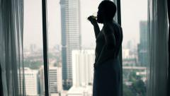 Young man drinking wine and admire view from window Stock Footage