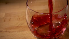 Cranberry juice pouring into glass, slow motion overhead view Stock Footage