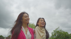 Attractive Asian female friends meet up and greet each other outdoors in city Stock Footage