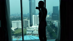 Young man in pants drinking coffee and admire view from window - stock footage