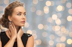 Beautiful woman wearing earrings over lights Stock Photos