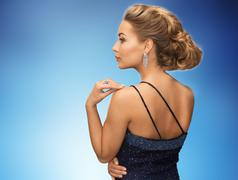 beautiful woman with diamond earring over blue - stock photo