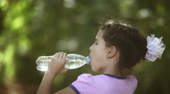 Teen girl drinks  water from  a plastic bottle on a green background  Stock Footage