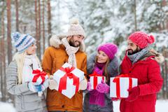 happy friends with gift boxes in winter forest - stock photo