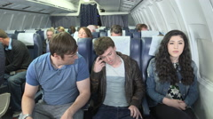 Male passenger on plane angry with friend who is scared of flying Stock Footage