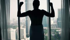 Young man in towel showing power concept standing by window Stock Footage