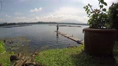 Rod fisherman onboard bamboo raft Stock Footage