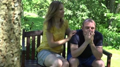Woman comfort friend for loss of job. Couple on bench in park. 4K Stock Footage