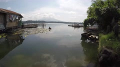 Man cleaning polluted lake of debris and algae Stock Footage
