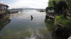 Man cleaning polluted lake of debris and algae - stock footage