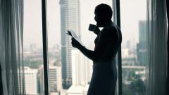 Young man in towel reading magazine and drinking coffee by window Stock Footage