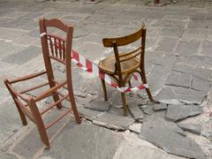 Two destroyed chairs standing on the hollow sidewalk. - stock photo