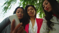 Attractive Asian female friends looking at mobile phone outdoors in the city Stock Footage