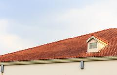 Chimneys on roof of red tiles with blue sky and clouds. Stock Photos