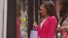 Attractive Asian female friends window shopping in the city - stock footage